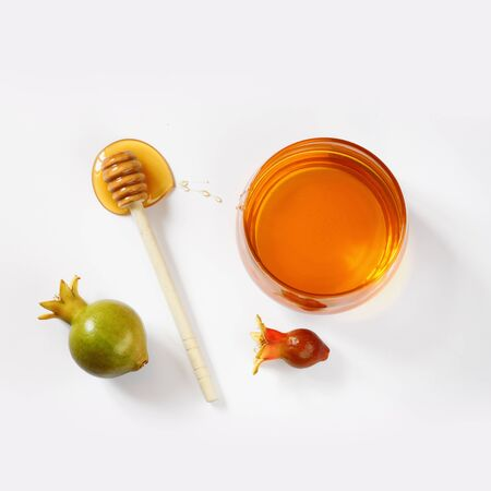 tova: rosh hashanah jewesh holiday concept  honey and pomegranate isolated on white. traditional holiday symbols.