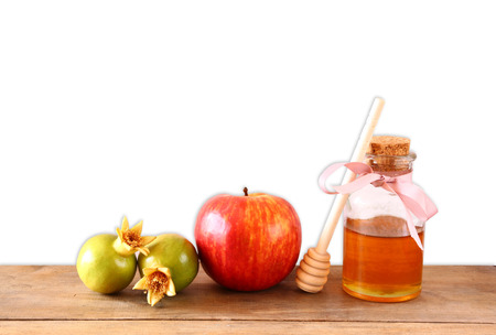 honey apple: rosh hashanah jewesh holiday concept  honey apple and pomegranate over wooden table. traditional holiday symbols.