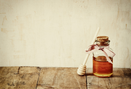 tova: abstract filtered image of honer glass jar. rosh hashanah jewesh holiday concept.  traditional holiday symbols.