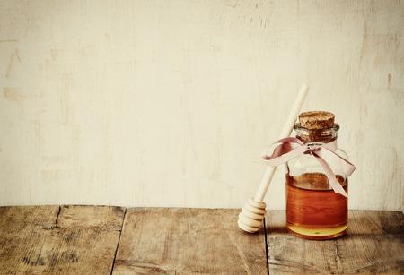 abstract filtered image of honer glass jar. rosh hashanah jewesh holiday concept.  traditional holiday symbols.