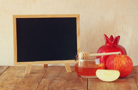 rosh hashanah: rosh hashanah jewesh holiday concept  blackboard honey apple and pomegranate over wooden table. traditional holiday symbols.