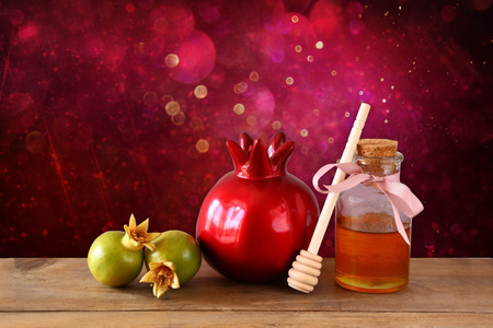 rosh: rosh hashanah jewesh holiday concept  honey and pomegranate over wooden table. traditional holiday symbols. Stock Photo