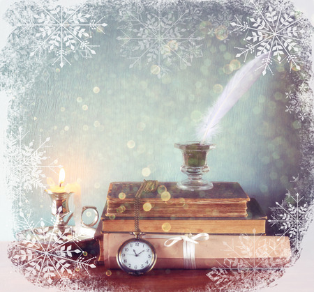 christmas candle: image of white Feather, inkwell and ancient books on old wooden table with snowflakes overlay
