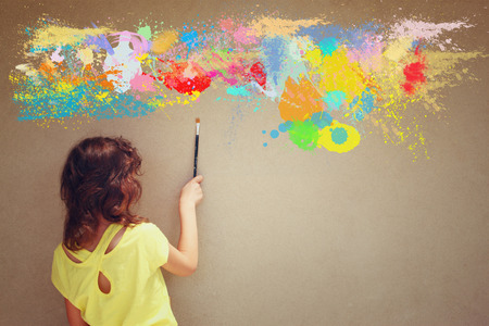 back view cute kid holding brush next to textured wall and paint splashes