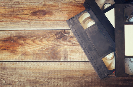 video cassette tape: stack of VHS video tape cassette over wooden background. top view photo. retro style image
