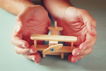 juguetes de madera: close up photo of mans hand holding wooden toy airplane over wooden background. filtered image. aspiration and simplicity concept