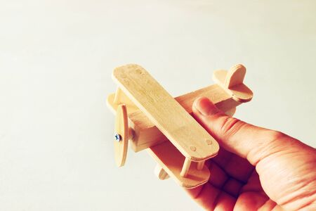 close up photo of mans hand holding wooden toy airplane over wooden background. filtered image. aspiration and simplicity concept