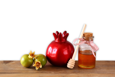 rosh hashanah: rosh hashanah jewesh holiday concept - honey and pomegranate over wooden table and isolated on white background. traditional holiday symbols.