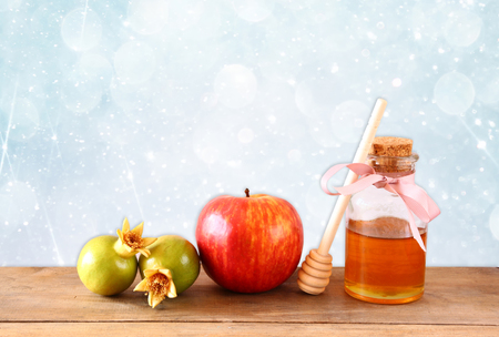 rosh hashanah jewesh holiday concept  honey apple and pomegranate over wooden table. traditional holiday symbols.