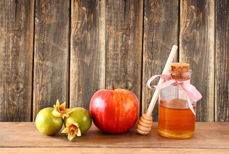 judaic: rosh hashanah jewesh holiday concept  honey apple and pomegranate over wooden table. traditional holiday symbols.
