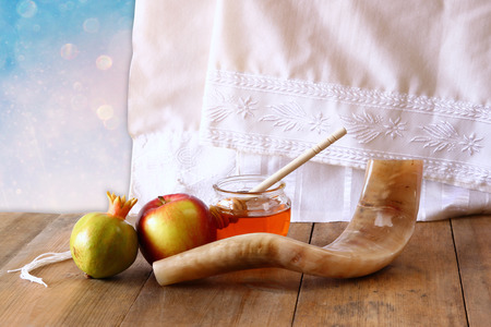 honey apple: rosh hashanah jewesh holiday concept - shofar, honey, apple and pomegranate over wooden table. traditional holiday symbols. Stock Photo