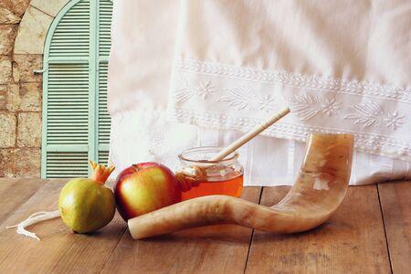 rosh hashanah jewesh holiday concept - shofar, honey, apple and pomegranate over wooden table. traditional holiday symbols. Stock Photo