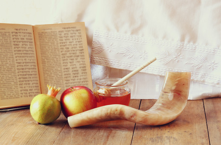 rosh hashanah jewesh holiday concept - shofar, torah book, honey, apple and pomegranate over wooden table. traditional holiday symbols. Stock Photo