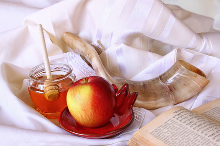 honey apple: rosh hashanah jewesh holiday concept - shofar, torah book, honey, apple and pomegranate over wooden table. traditional holiday symbols. Stock Photo