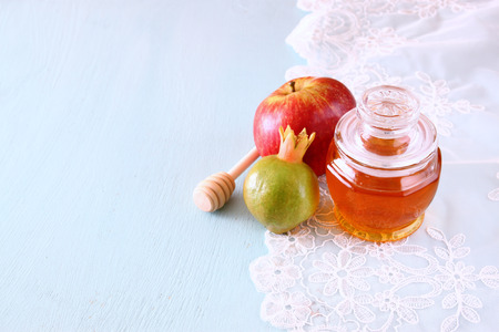 rosh: rosh hashanah jewesh holiday concept - honey, apple and pomegranate over wooden table. traditional holiday symbols.