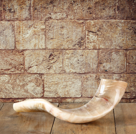 rosh: shofar horn on wooden table in front of jerusalem ancient wall. rosh hashanah jewish holiday concept . traditional holiday symbol. Stock Photo