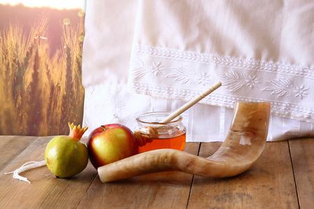 shofar: rosh hashanah jewesh holiday concept  shofar honey apple and pomegranate over wooden table. traditional holiday symbols. Stock Photo