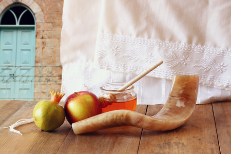 honey apple: rosh hashanah jewesh holiday concept  shofar honey apple and pomegranate over wooden table. traditional holiday symbols. Stock Photo