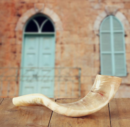 yom: shofar horn on wooden table in front of jerusalem ancient window. rosh hashanah jewish holiday concept . traditional holiday symbol.