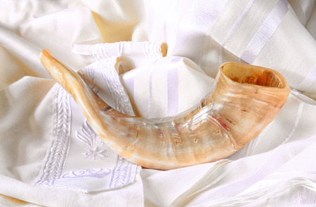jewish culture: shofar horn on white prayer talit. rosh hashanah jewish holiday concept . traditional holiday symbol.