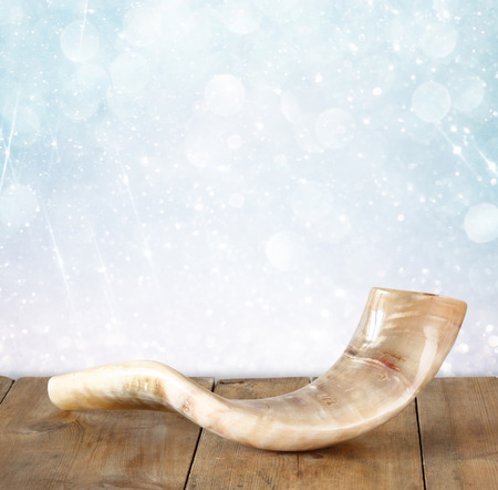shana tova: shofar horn on wooden table. rosh hashanah jewish holiday concept . traditional holiday symbol. Stock Photo