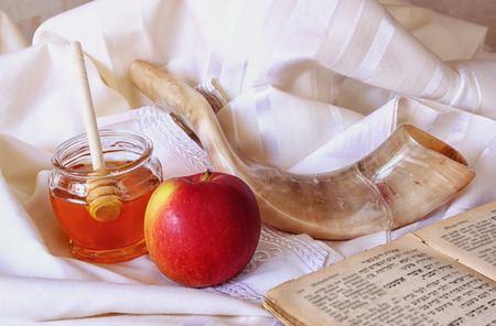 rosh hashanah jewesh holiday concept  shofar torah book honey apple and pomegranate over wooden table. traditional holiday symbols. Stock Photo