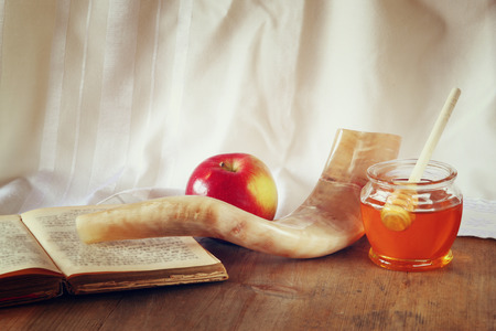 jewish: rosh hashanah jewesh holiday concept  shofar torah book honey apple and pomegranate over wooden table. traditional holiday symbols. Stock Photo