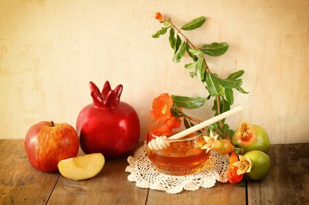 rosh hashanah jewesh holiday concept - honey and pomegranate over wooden table. traditional holiday symbols. Stock Photo