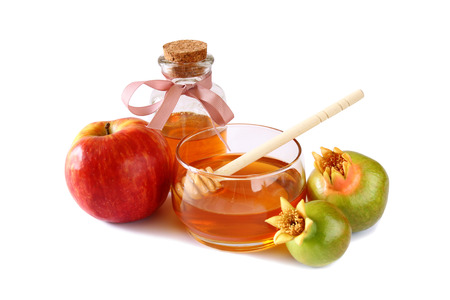 honey apple: rosh hashanah jewesh holiday concept  honey apple and pomegranate isolated on white. traditional holiday symbols.