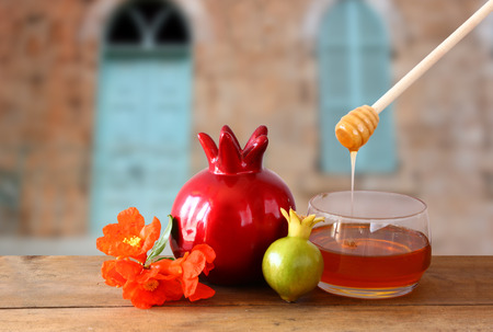 rosh hashanah jewesh holiday concept - honey and pomegranate over wooden table. traditional holiday symbols. Imagens