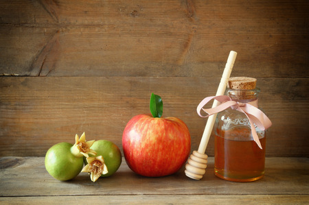 rosh hashanah jewesh holiday concept - honey, apple and pomegranate over wooden table. traditional holiday symbols.