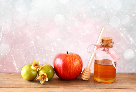 honey apple: rosh hashanah jewesh holiday concept - honey, apple and pomegranate over wooden table. traditional holiday symbols.