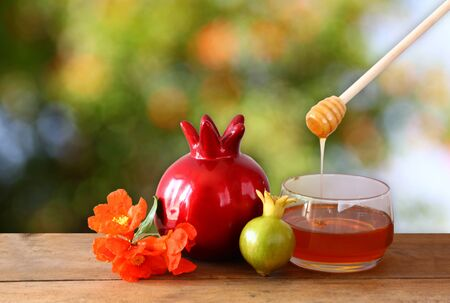 tova: rosh hashanah jewesh holiday concept  honey and pomegranate over wooden table. traditional holiday symbols. Stock Photo