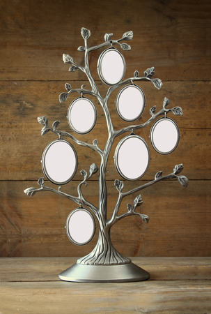 Image of vintage antique classical frame of family tree on wooden table Stock Photo