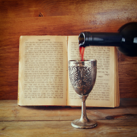 sephardic: vintage shabbath silver cup of wine in front of torah prayer book Stock Photo