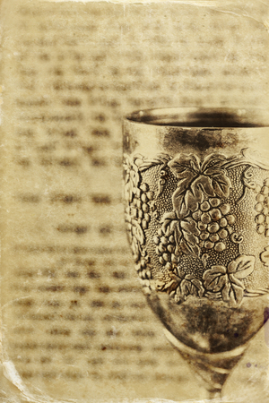 ancient israel: vintage shabbath silver cup of wine in front of torah prayer book. old photo style image