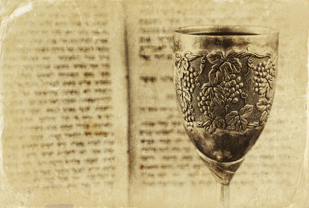 prayer book: vintage shabbath silver cup of wine in front of torah prayer book. old photo style image