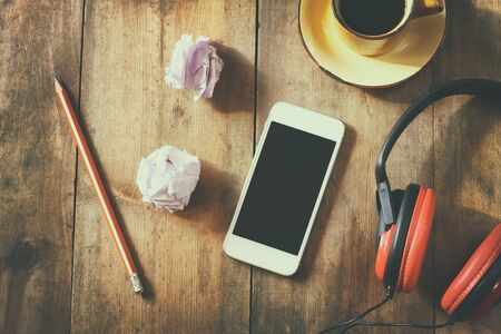image style: top view image of smartphone with blank screen headphones and coffee cup. room for text . faded style image