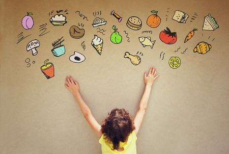 food illustration: back view of cute kid imagine various foods with set of infographics over textured wall background Stock Photo