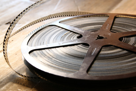 family movies: top view image of old 8 mm movie reel over wooden background