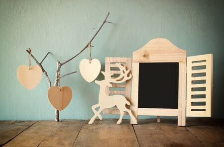 old photograph: decorative chalkboard frame and wooden hanging hearts over wooden table. ready for text or mockup