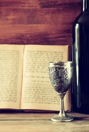 kiddush: vintage shabbath silver cup of wine in front of torah prayer book Stock Photo