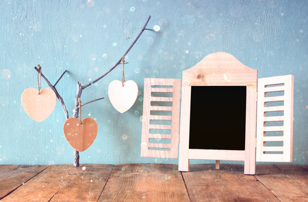 hearts background: decorative chalkboard frame and wooden hanging hearts over wooden table. ready for text or mockup. retro filtered image