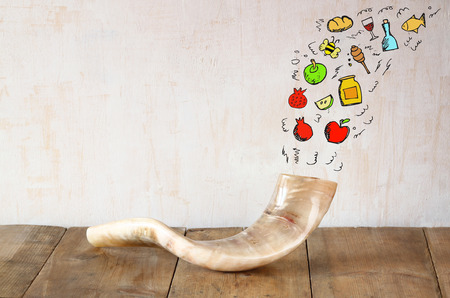 shana tova: shofar horn on wooden table with set of infographics over textured background. rosh hashanah jewish holiday concept . traditional holiday symbol. Stock Photo