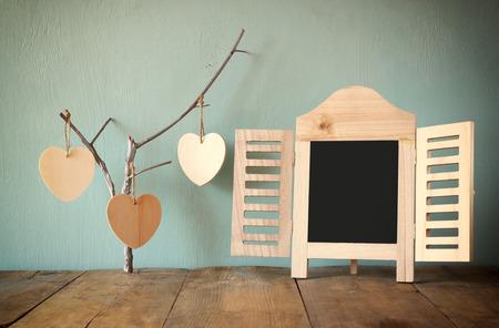 Cadre de tableau décoratif et coeurs suspendus bois sur la table en bois. prêt pour le texte ou maquette. rétro image filtrée Banque d'images - 43067648
