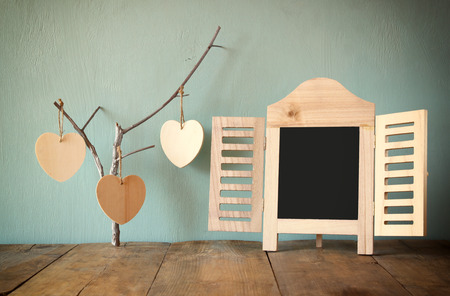 romantic picture: decorative chalkboard frame and wooden hanging hearts over wooden table. ready for text or mockup. retro filtered image