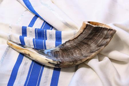 holiday symbol: shofar horn on white prayer talit. room for text. rosh hashanah jewish holiday concept . traditional holiday symbol.