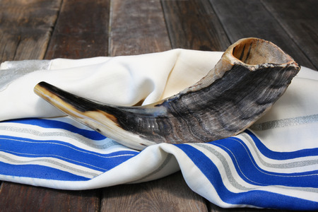 jewish symbols: shofar horn on white prayer talit. room for text. rosh hashanah jewish holiday concept . traditional holiday symbol.