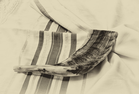 kippur: shofar horn on white prayer talit. room for text. rosh hashanah jewish holiday concept . traditional holiday symbol.