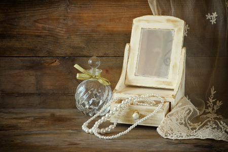 mirror image: vintage pearls , antique wooden jewelry box with mirror and perfume bottle on wooden table. filtered image Stock Photo